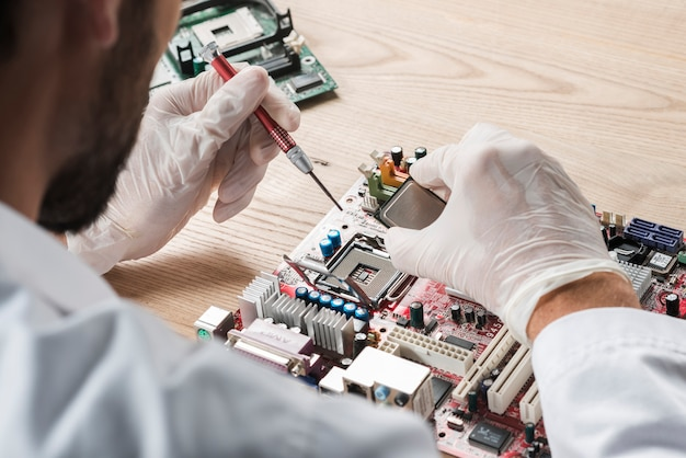 コンピュータのマザーボードで働く男性技術者