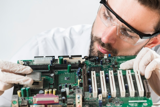 コンピュータのマザーボードにチップを挿入して安全メガネを着用している男性技術者のクローズアップ