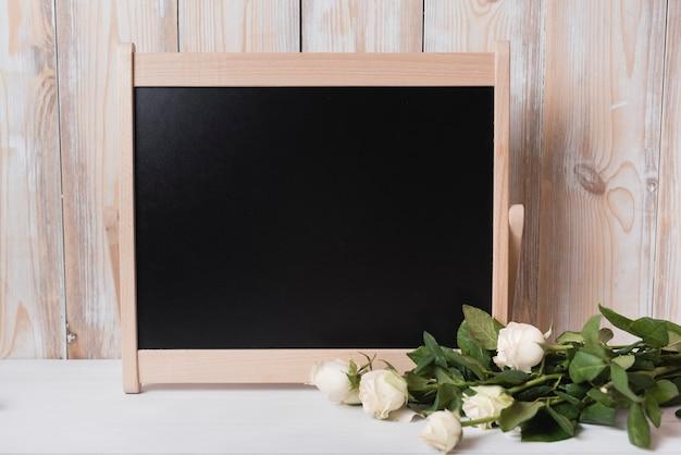 白い机の上に木製の小さな黒板とバラの束