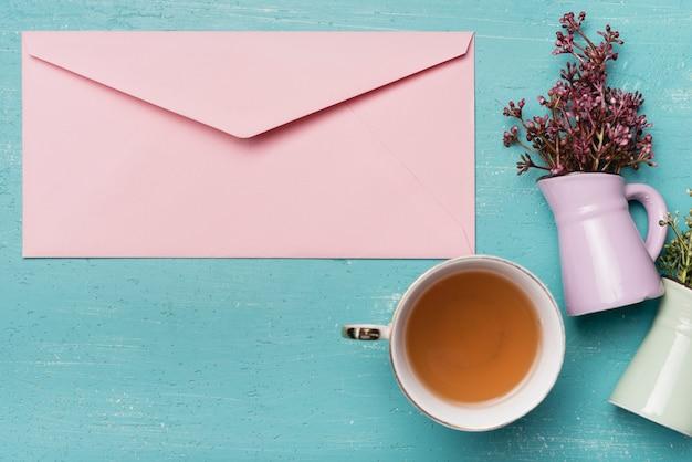 青い木製の背景に花瓶とお茶カップとピンクの閉じた封筒