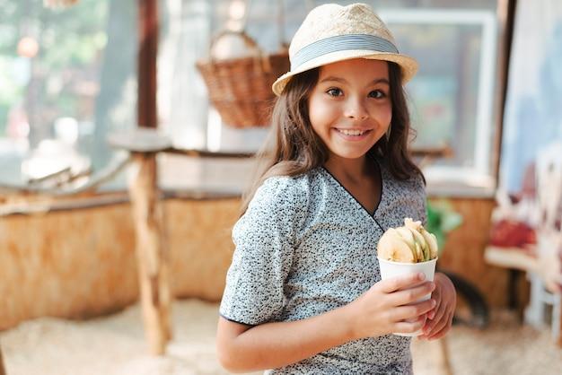 動物園でリンゴスライスのガラスを保持している笑顔の女の子の肖像
