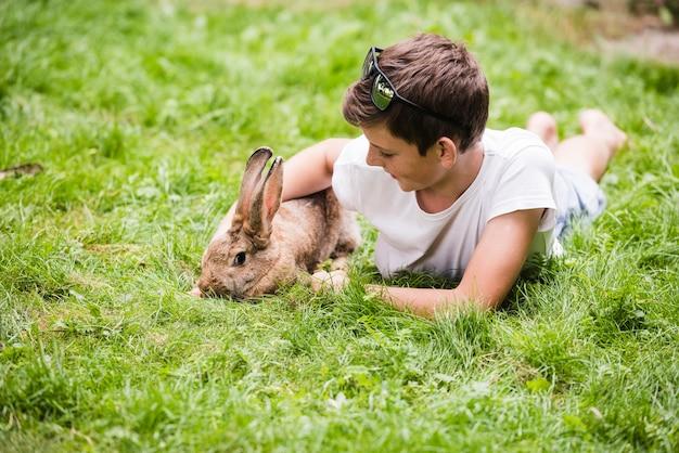 青い草の上に彼のペットのウサギと横たわっている少年