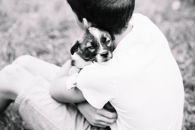 彼の素敵な子犬を抱きしめている少年のオーバーヘッドビュー