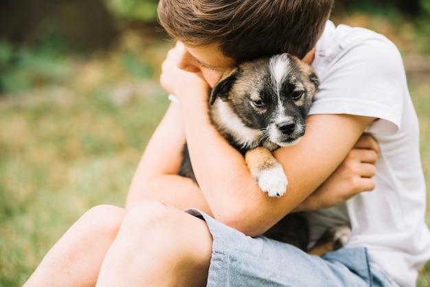 Крупный план мальчик обнимает его прекрасный щенок