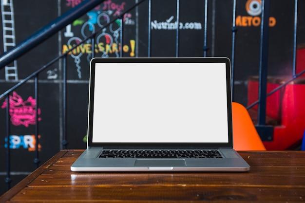 レストランでテーブルの上に白い空白の画面を持つラップトップ