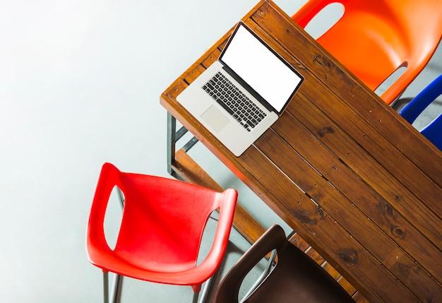 カラフルな椅子を持つ木製テーブル上の開いたラップトップのオーバーヘッドビュー