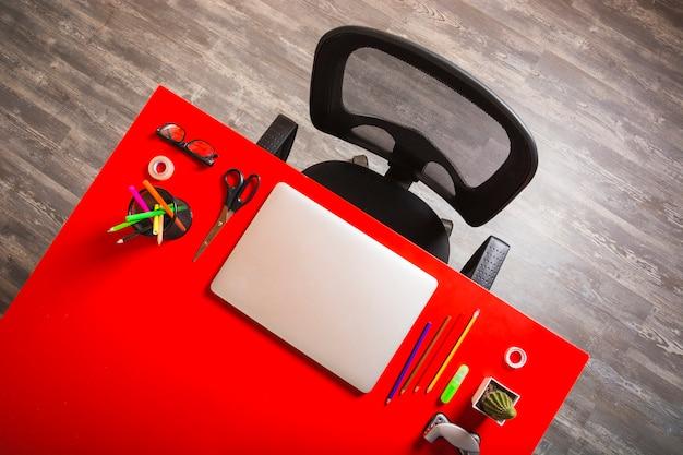 ノートパソコンと赤いテーブル上の文房具とオフィスの職場で空の黒い椅子