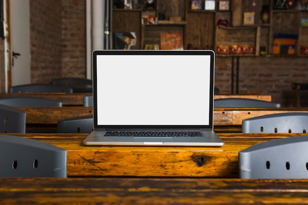 カフェの木製テーブルの上に白いディスプレイスクリーン付きラップトップ