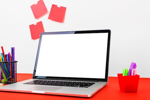 赤いテーブルにカラフルな文房具と白い画面を表示するラップトップ