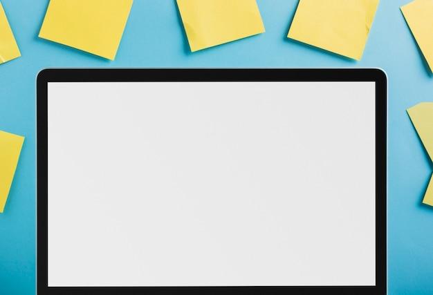 Ноутбук с пустым белым экраном, окруженный желтыми клейкими нотами