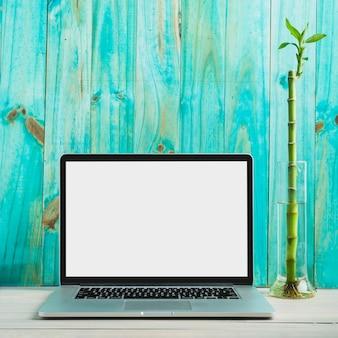 木製の机の上に白いスクリーンが空いているラップトップ