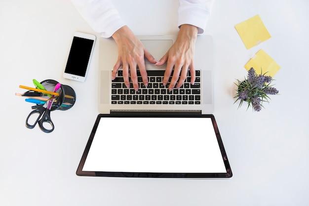 デスクでラップトップを使用しているビジネスマンの手の高さのビュー