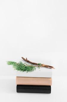 白い背景にある別のカバーと本のスタックに小枝のクローズアップ