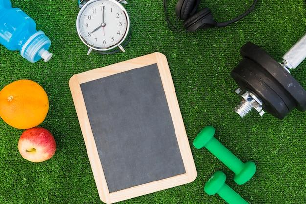 フルーツ;水びん;目覚まし時計;ヘッドホン;緑の芝生で木製の空白のスレートにダンベル