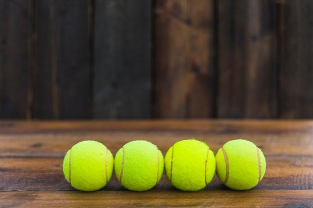 木製のテクスチャの背景に緑色のテニスボールの行