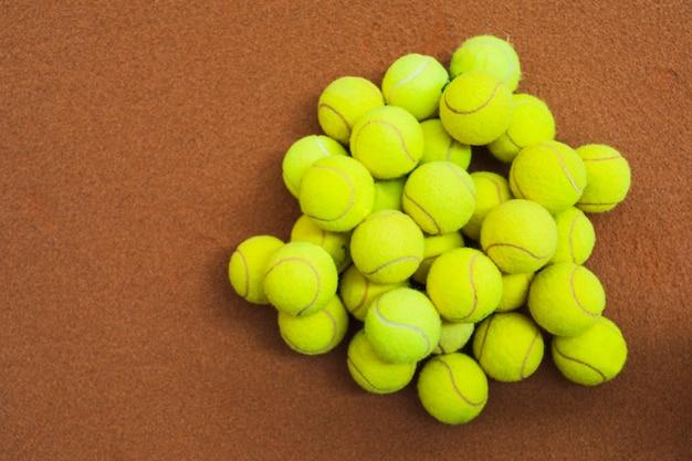 テニスコートに緑のテニスボールのヒープ