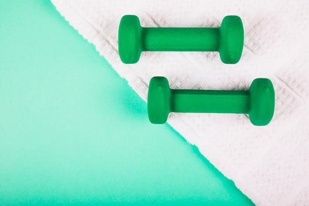 白いナプキンの緑色のダンベル、ターコイズブルーの背景