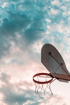 曇った空に対してバスケットボールフープの低い角度のビュー