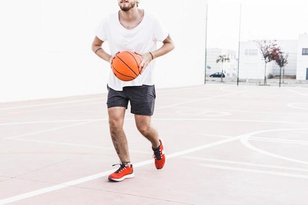 バスケットボールで走っている男