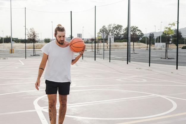 屋外の裁判所でバスケットボールを持っている男