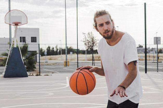 Молодой человек подпрыгивает баскетбол в суде
