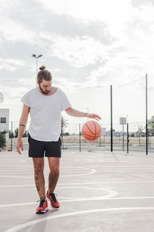 コートにバスケットボールをドリブルするプレーヤー