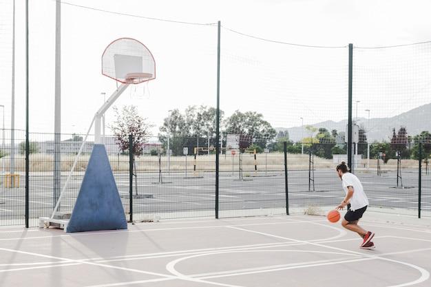 屋外のコートでは、フープの近くでバスケットボールを練習している男