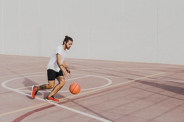 屋外のコートにバスケットボールを練習している若い男