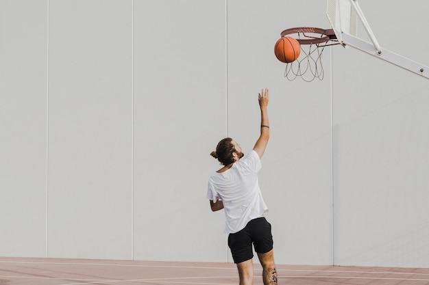フープでバスケットボールを投げている若い男のリアビュー