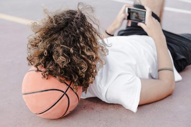 Человек склоняется к баскетболу, используя мобильный телефон