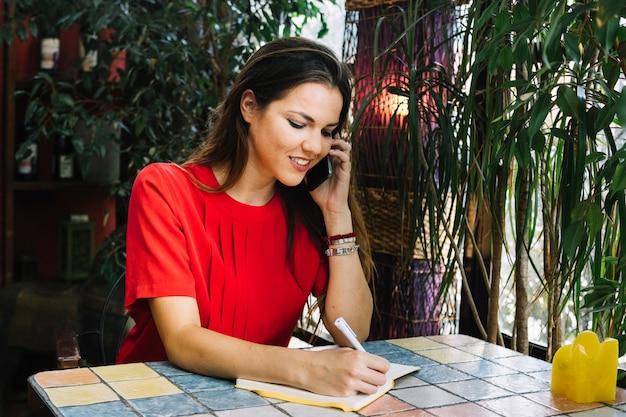 携帯電話で話しているときに日記でスケジュールを書く美しい女性