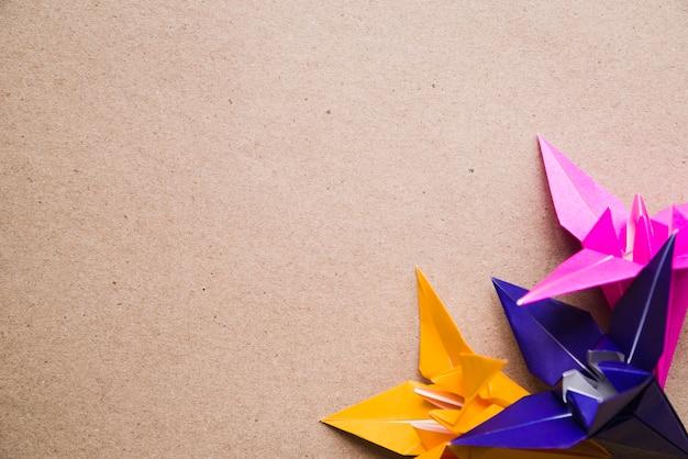 段ボールのテクスチャの背景に折り紙のカラフルな紙の花