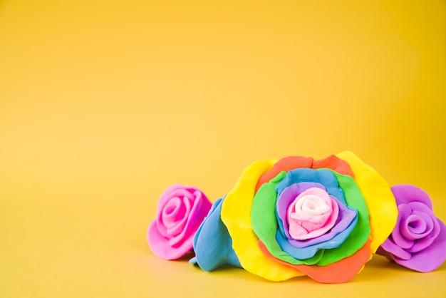 黄色の背景に粘土で作られた大きな創造的な美しいバラ