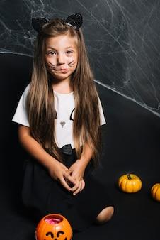 ジャック・オ・ランタンのバケツの近くに座っている猫の衣装でおかしい女の子