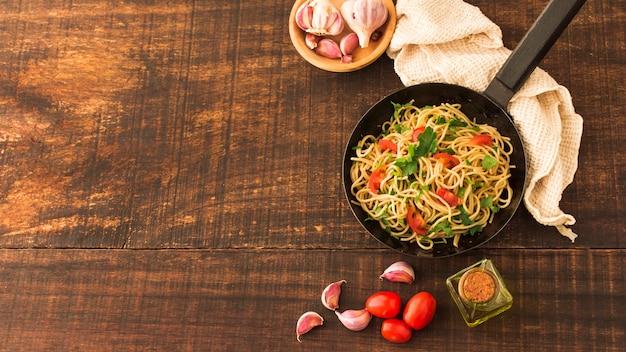 木製の背景にトマトとニンニクのクローブを入れたスパゲッティパスタ