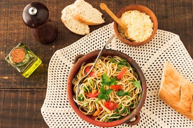 Верхний вид спагетти-пасты на глиняной посуде с сыром и хлебом на деревянном столе