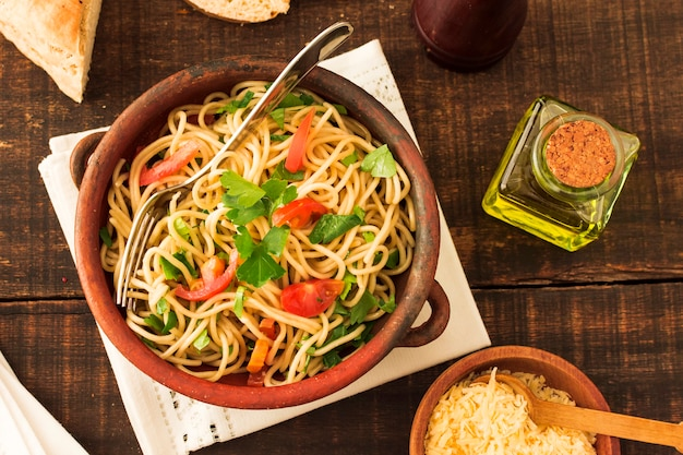 陶器のスパゲティパスタ上のトマトとコリアンダーのトッピング