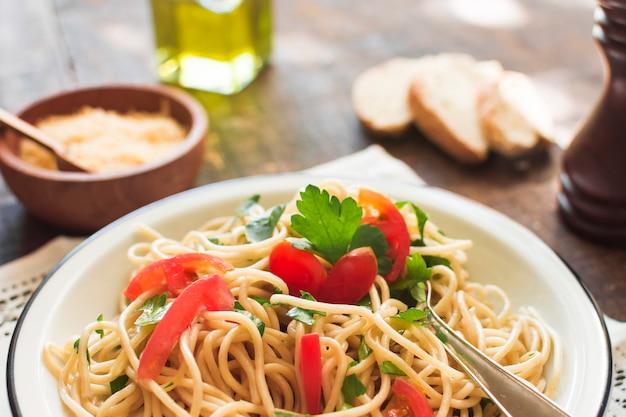 Крупный план спагетти с помидорами и листьями кориандра на тарелке