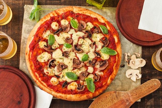 トマトソース入りのマーゲリータ焼きピザ。チーズ;バジル、マッシュルーム