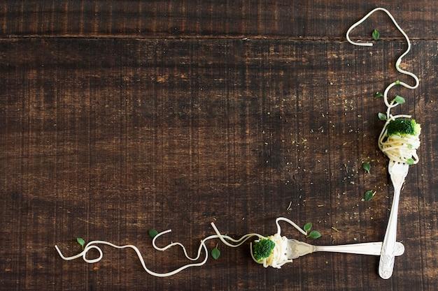 ブロッコリーと木製のテクスチャの背景に麺とフォーク