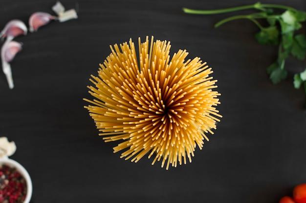 黒背景に束に集まった全粒小麦のスパゲッティの花