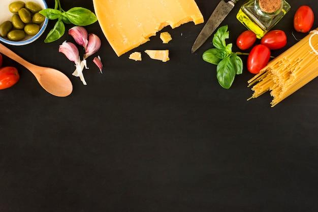 野菜と黒の背景にチーズとパスタ
