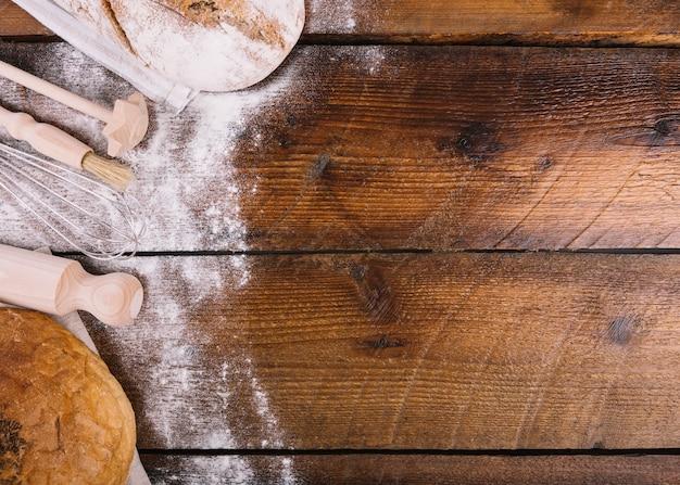 木製テーブル上の機器とパンと小麦粉