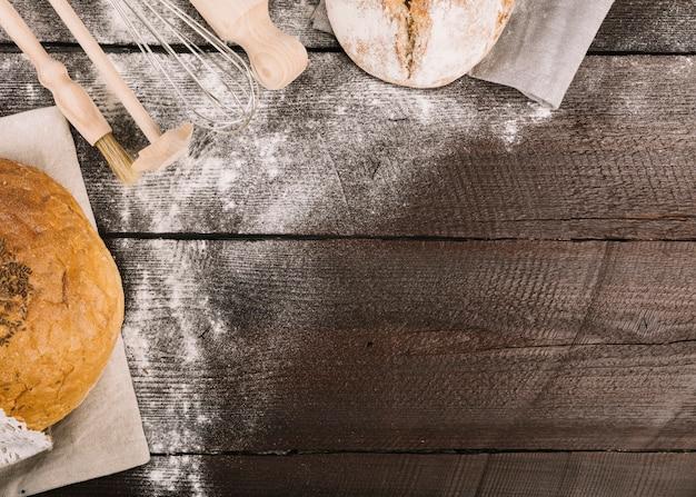 木製の厚板に小麦粉を散らしたパンと台所用具
