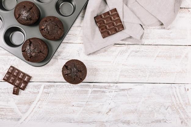 白い木製のテーブルにチョコレートのカップケーキ