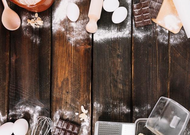 キッチン用品と木製の板の背景にケーキを焼くための材料