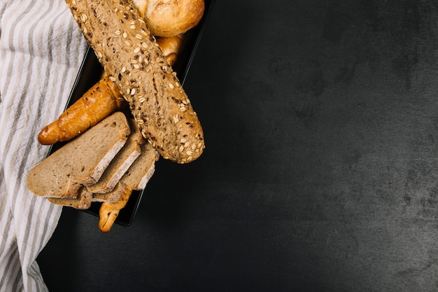 黒のキッチンのワークトップにナプキンを焼いた全粒パン