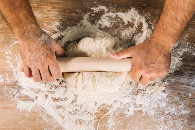 木製のテーブルにローリングピンで生地を平らにする男性のパン屋の手のトップビュー