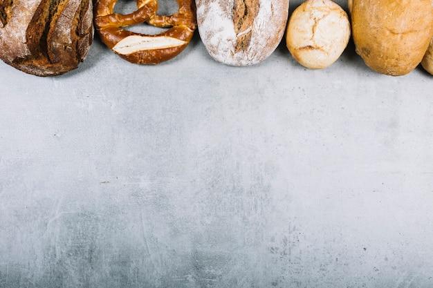 グランジの背景にさまざまな種類のパンで作られた一番上の行