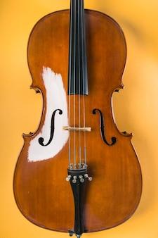 黄色の背景に弦を持つ木製のバイオリン